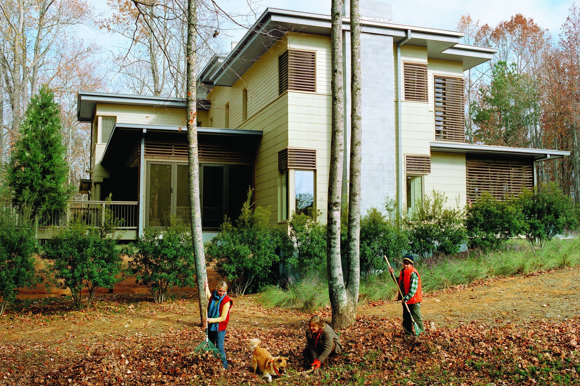 Family raking autumn leaves
