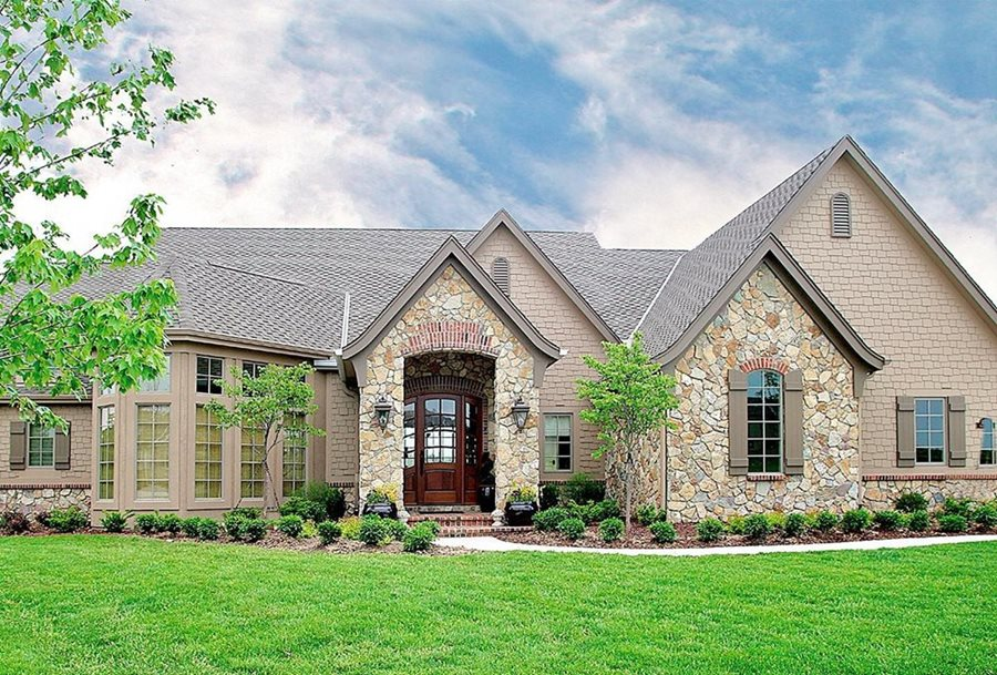 A french country house with shake siding and rustic cut brown stone.