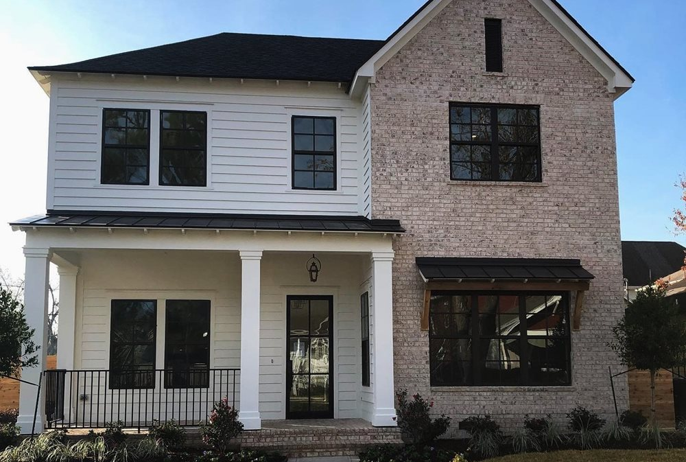 A neutral siding and stone color palette with white siding, red-ish brick and black windows.