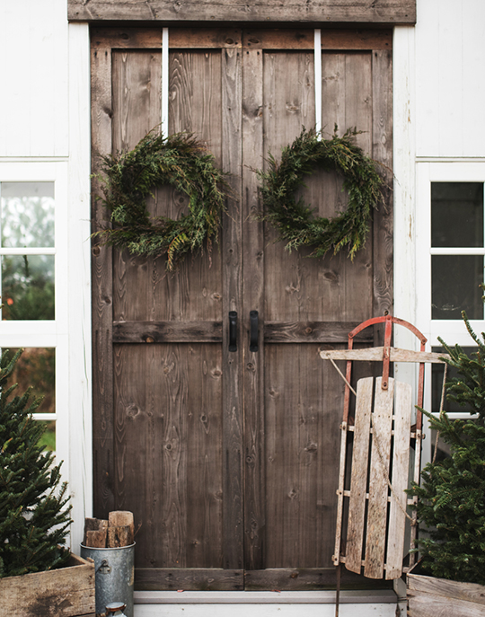 Brown-Sled-Leaning-On-Large-Wooden-Double-Doors-With-Green-Holiday-Wreaths-And-Evergreen-Trees