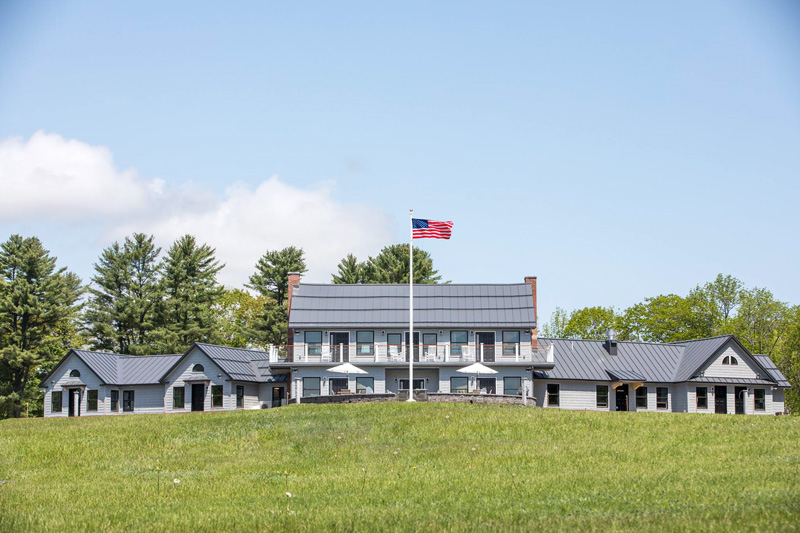 Travis-Mills-Veterans-Retreat-Building-In-White-James-Hardie-Fiber-Cement-Siding-With-Raised-American-Flag-With-Blue-Sky-And-Puffy-White-Clouds
